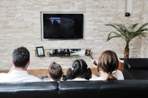 family wathching flat tv at modern home indoor